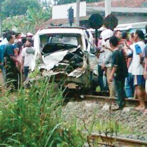 Warga menyaksikan mobil yang risek dihajar kereta.