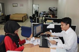 LAYANI NASABAH: Pegawai Bank BRI Juanda Bekasi khusus pelayanan BPJS Kesehatan, sedang melayani nasabah yang mengurus kartu peserta BPJS Kesehatan. OKE/RADAR BEKASI