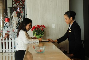LAYANI TAMU: Resepsionis Hotel Santika Premiere Kota Harapan Indah Bekasi (kanan) sedang melayani tamu yang ingin menginap. OKE/RADAR BEKASI