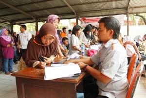 PEMBAGIAN PSKS: Pegawai PT Pos Indonesia kantor cabang Bekasi sedang melayani warga yang mengambil dana PSKS tahap pertama.OKE/RADAR BEKASI