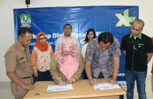 TANDA TANGAN: Sales Manager XL area Bekasi, Heriantoni (kanan) bersama Kabid UMKM Disperindagkop Kota Bekasi, Herlia Susilawati (kiri) melakukan penandatanganan sertifikat workshop digitalisasi. OKE RADAR BEKASI