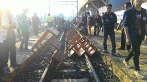 Nampak penumpang KRl Commuter Line memblokir rel kreta api.