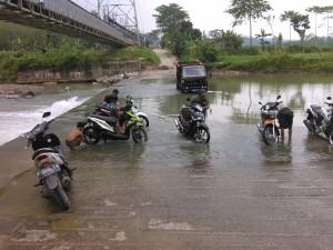 BUTUH JEMBATAN : Warga memanfaatkan Sungai Cileungsi yang selama ini di jadikan jalur penyeberangan dari Kampung Pasir Randu, Desa Gunungsari ke Desa Lulut untuk mencuci motor, kemarin.