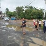 KERJA BAKTI: Warga Desa Sukamaju, Kecamatan Megamendung, kerja bakti membuang air yang menutupi lubang di jalan alternatif Gado-Cikopo, Senin.