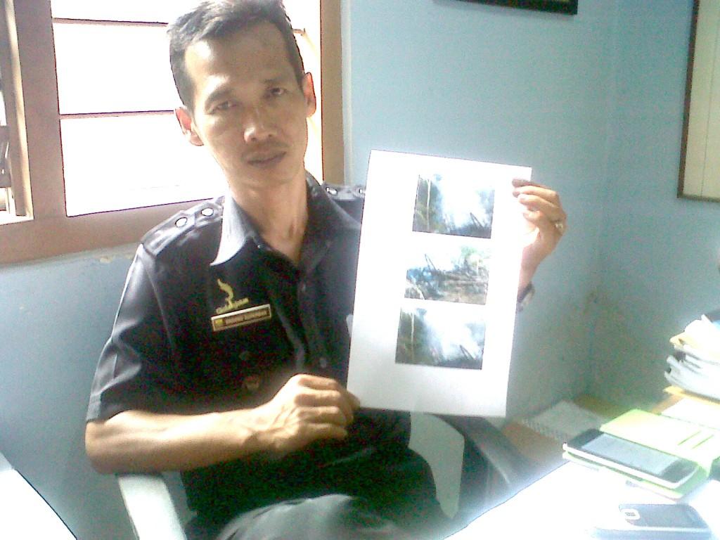 PRIHATIN : Kades Gudang, Endang Suparman memperlihatkan foto bangunan Eman yang ludes terbakar satu bulan lalu.