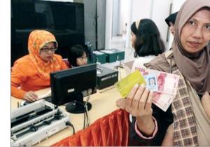 SUMRINGAH: Seorang warga Depok usai mencairkan dana PSKS di Kantor Pos Depok, November lalu