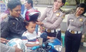 BAGIKAN HELM: Salah seorang Perwira di Kantor Samsat Cinere sedang memberikan helm kepada salah seorang anak pengendara sepeda motor, kemarin