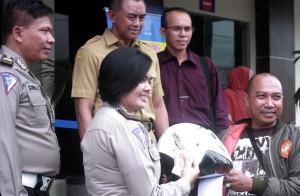 HADIAH : Salah satu wajib pajak mendapat hadiah helm yang diberikan pihak Samsat Kota Bekasi.Risky/RADAR BEKASI