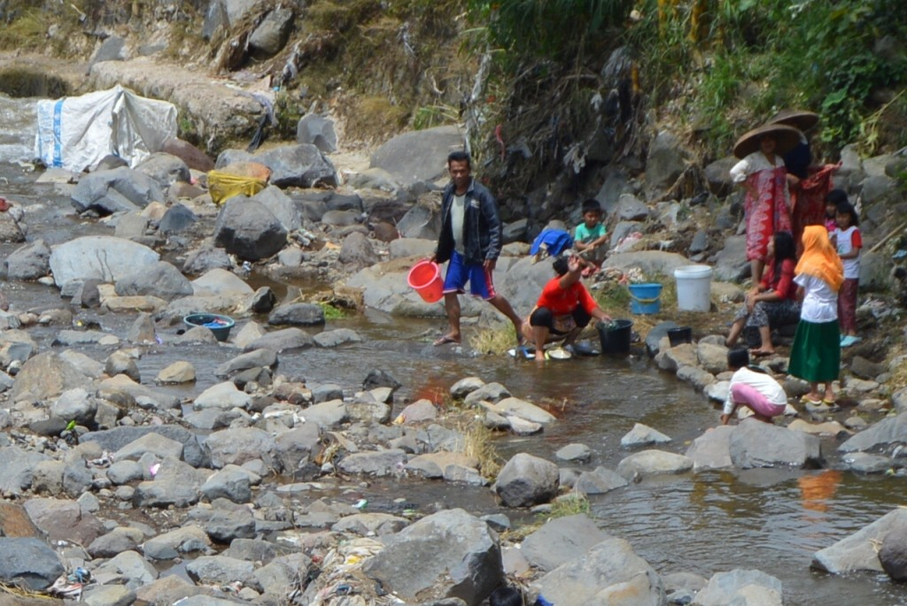 KRISIS: Warga Cisarua Pacet terpaksa MCK di sungai akibat kurang air bersih. Foto : Farhan/Radar Cianjur/Pojoksatu.id