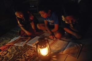 BUTUH LISTRIK: Tiga anak membaca buku dengan diterangi lampu minyak. Kondisi ini masih terjadi di beberapa daerah di Kabupaten Bogor.