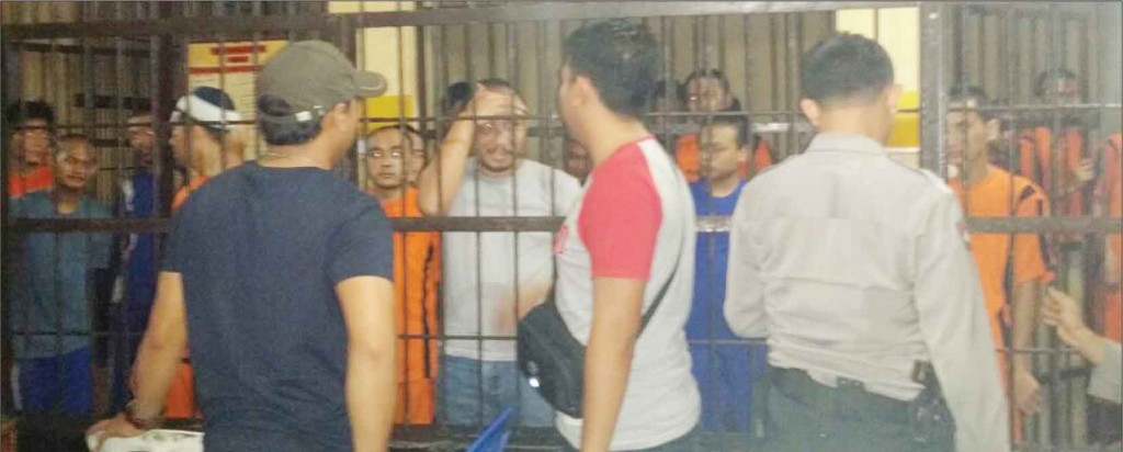 MALU: Oknum KPK (berkumis dan memakai kaos warna abu-abu, red) yang diduga menipu korbannya seorang guru honorer kini berada di balik jeruji Makopolres Sukabumi Kota, Senin (27/7/2015).