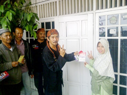 GERILYA: Bobotoh Marwan-Adjo saat menempelkan stiker ke rumah-rumah warga di Sukaraja.