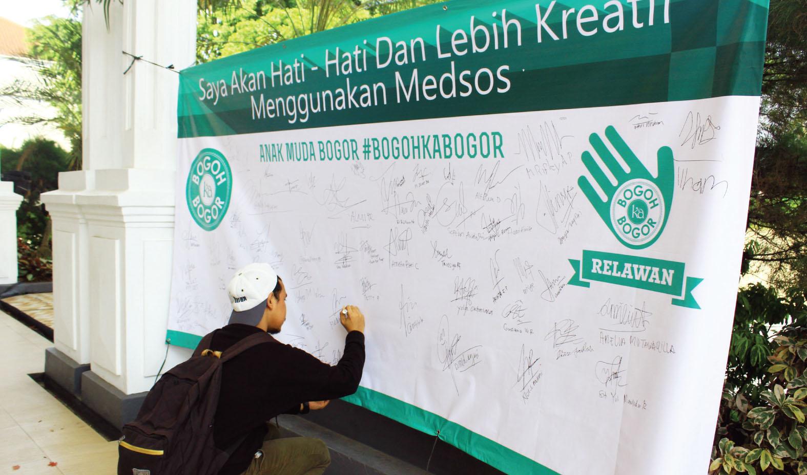 KOMITMEN: Seorang remaja sedang menandatangani poster yang berisi tagline ''Saya akan hati-hati dalam menggunakan media sosial. FOTO : Maya / Radar Bogor.