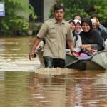 NAIK PERAHU: Petugas Badan Penanggulangan Bencana Daerah (BPBD) Kota Bekasi menggunakan perahu untuk membantu ibu-ibu menuju rumah mereka saat banjir melanda perumahan Bumi Nasio di Jatikramat, Jatiasih, Senin (7/12). Banjir tersebut disebabkan oleh jebolnya tanggul dan air kiriman dari Kali Cikeas, sehingga memenuhi pemukiman warga.FOTO: ARIESANT/RADAR BEKASI