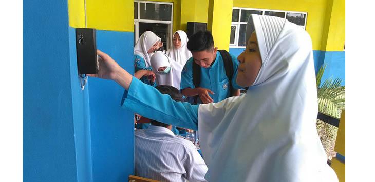 TEKNOLOGI: Siswa SMK Dharma Kusuma Cianjur sedang melakukan absen masuk sekolah yang langsung terkirim ke orang tua.