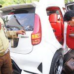 MELAKUKAN PENGECEKAN: Petugas sedang memeriksa barang bukti kasus First Travel berupa kendaraan mobil di halaman Kantor Kejaksaan Negeri Kota Depok. Ahmad Fachry/Radar Depok