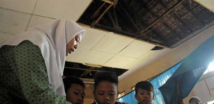 Sejumlah siswa dan siswi SDN Sirnajaya 02 tetap fokus belajar di ruang kelas yang kondisi atapnya telah rusak di Kecamatan Serangbaru, Kabupaten Bekasi, kemarin. Foto Ariesant/Radar Bekasi