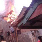 GUNAKAN TANGGA: Sejumlah kerabat pemilik rumah berusaha memadamkan api yang makin membesar dengan alat seadanya. Sementara itu, kobaran api yang relatif besar membuat sejumlah warga enggan mendekati bangunan.