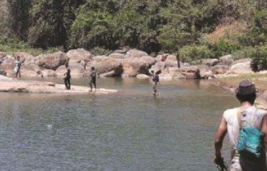 OBJEK WISATA : Salah seorang warga tengah menunjukan tulisan dalam ukiran batu yang menjulang di lokasi Sungai Cikarang.