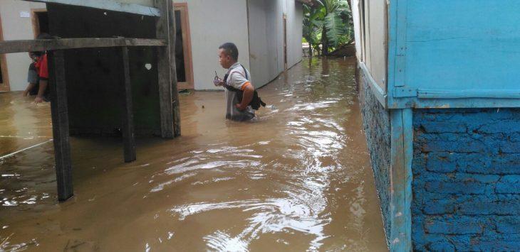 Warga saat mencoba melintasi ditengah banjir. Foto: pey/pojokjabar