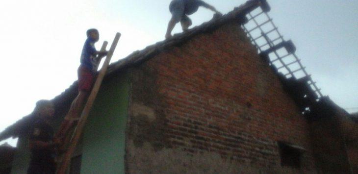 Warga Karyamulya sedang memperbaiki genteng rumahnya akibat terkena tiupan angin kencang yang menyerang pemukiman sekitar pukul 15:00 WIB. Foto: Alwi/pojokjabar.com