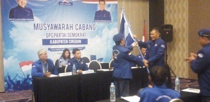 Plt Ketua Partai Demokrat Kab Cirebon H. Nana Karnadi (kanan) menyerahkan pataka Partai Demokrta kepada ketua terpilih Muklisi. Foto: Bagja/pojokjabar