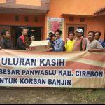 Komisioner Panwaskab Cirebon, Rahmat Hidayat (kanan) secara simbokis tengah memberikan bantuan kepada perwakilan Panwascam Ciledug. Foto: Bagja/pojokjabar