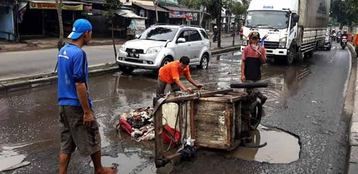 Sebuah gerobak sampah terguling saat melintas di jalur berlubang Jalan Raya I Gusti Ngurah Rai, Kranji, Bekasi Barat, Kamis (22/2). Foto Raiza Septianto/Radar Bekasi
