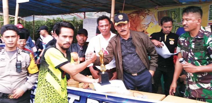 BERIKAN PIALA: Umuh Muchtar saat memberikan piala penghargaan kepada salah satu pemenangan Turnamen Pamulihan Cup. TOHA RAMDANI/RADAR SUMEDANG