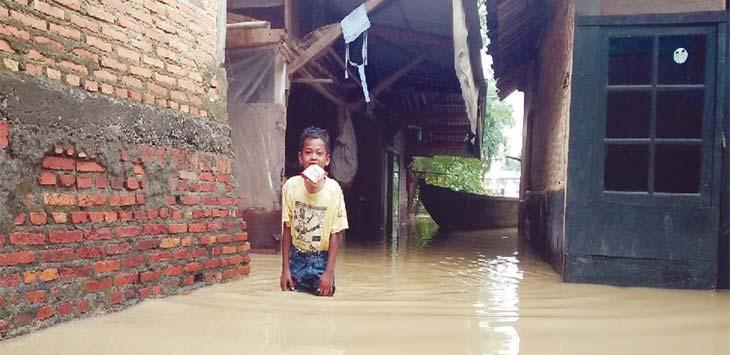 TIDAK SEKOLAH: Rendi Nurfadilah (12), warga Kampung Bentengpulopasir RT 06 RW 08, Kelurahan Tanjungmekar, Kecamatan Karawang Barat, tidak sekolah karena seluruh perlengkapan sekolahnya terendam. ASEP KURNIA/RADAR KARAWANG