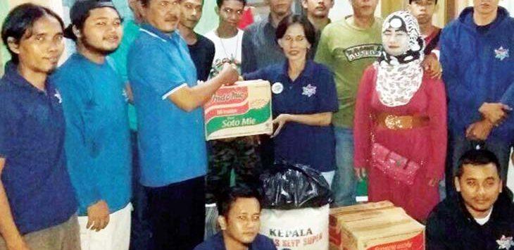 BERI BANTUAN : Pendiri Komunitas KAMI ADA, Adi Suman (paling kiri) bersama pengurus, Ketua RW1 Pondok Cina dan korban banjir menyerahkan bantuan. Irwan/Radar Depok