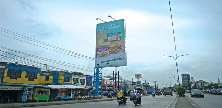 PAPAN REKLAME: Sejumlah pengendara melintas di bawah papan reklame yang diduga tak berizin di Jalan Teuku Umar Cibitung, Kabupaten Bekasi, Selasa (13/3/18). ARIESANT/RADAR BEKASI