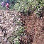 KEMBALI BERGESER: Warga Kampung Rawabakti melintasi jalan kampung yang ambles dan bergeser. Kampung Rawabakti merupakan kampung ketiga yang mengalami pergeseran tanah di Desa Sukawagi. Arifal/Radar Bogor
