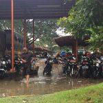 Seorang Pamdal Kabupaten Bekasi melewati banjir di belakang Gedung Bupati Bekasi. Foto : Enriko/Pojokjabar