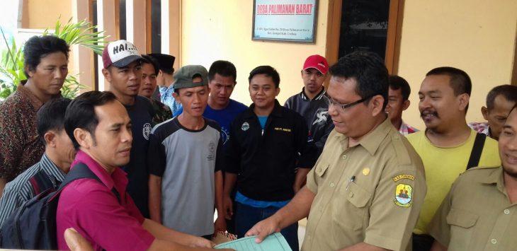 Ketua RW 13 Sumarno menyerahkan dokumen penolakan warga kepada Sekretaris Desa Palimanan Barat, Kadira. Foto: Bagja/pojokjabar.com