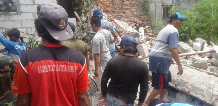 Warga tengah mengevakuasi runtuhan tembok. Foto: Dede/pojokjabar.com