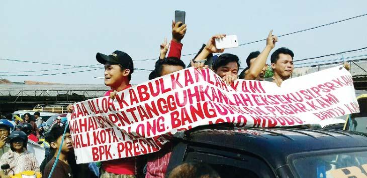 Para Pedagang Pasar Kemirimuka Membentangkan spanduk isi tolakan eksekusi pasar kemirimuka. Aji Hendro/Metro Depok