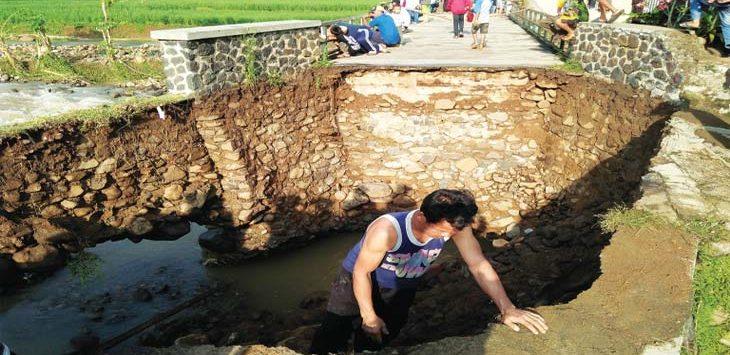 AMBLES: Ujung jembatan ambles karena tergerus air Sungai Cikoneng, yang meluap akibat hujan deras sejak Sabtu (21/4/18) sore. AGUN GUNAWAN/RADAR SUMEDANG