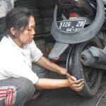 TANGGUH: Ade Mulyani (32), perempuan yang menjadi tukang tambal ban di sekitar lampu merah persimpangan Cirendang, Kabupaten Kuningan. Sudah 10 tahun Ade berprofesi yang lazimnya dilakoni laki-laki. Foto: M Taufik/Radar Kuningan