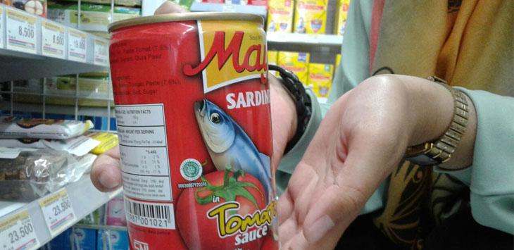 Warga menunjukkan ikan kaleng yang beredar pemberitaan di dalamnya terdapat cacing parasit. Foto: Alwi