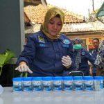 Seorang petugas BNN sedang merapihkan letak botol berisi urine./Foto: Adi
