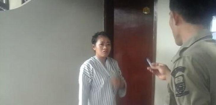 seorang wanita dengan rambut di belakang terikat saat marah-marah kepada Satpol PP ketika petugas memergokinya berduaan dengan laki-laki di dalam kamar hotel. Foto: Alwi