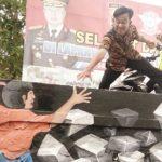 Warga bersama polisi saat mencoba lukisan tiga dimensi yang berada di tembok area pengujian kendaraan Satpas Polres Sukabumi, jalan Jendral Sudirman, Kelurahan/Kecamatan Palabuhanratu