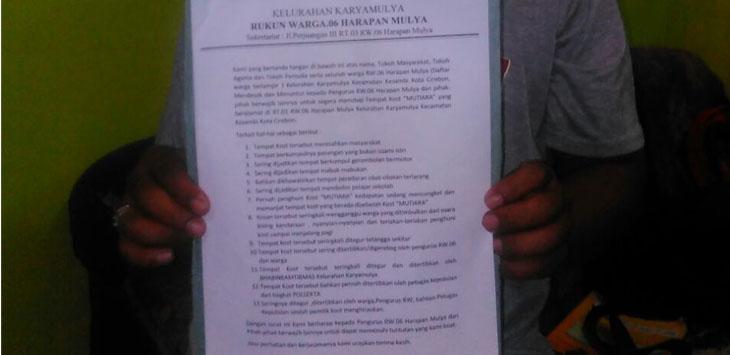 Seorang warga Harapan Mulya sedang menunjukkan surat pernyataan sikap dari unsur RT, RW, Linmas, DKM dan Ulama setempat atas adanya kost-kostan Mutiara yang diduga meresahkan. Foto: Alwi