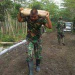 PENUH SEMANGAT: Anggota TNI tengah memikul semen untuk pembangunan jalan dalam program TMMD ke-101.