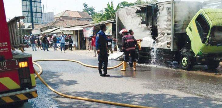 PADAMKAN API: Petugas pemadam kebakaran berusaha memadamkan api yang membakar mobil box. Gani/Radar Karawang