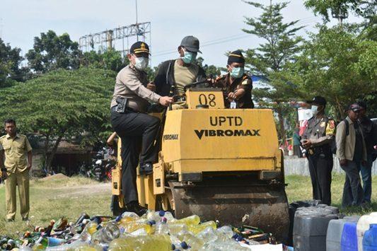 Ribuan botol Miras baik oplosan saat dimusnahkan satuan kepolisian dari Polres Cirebon Kota (Ciko) dengan menggunakan silinder di lapangan Kesenden Kota Cirebon. Foto: Alwi