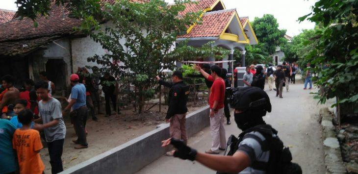 Seorang anggota dari Densus 88 Mabes Polri tampak berjaga-jaga mengamankan suasana saat penggeledahan rumah kontrakan terduga teroris di Desa Jemaras Kidul, Kecamatan Klangenan, Kabupaten Cirebon. Foto: Alwi