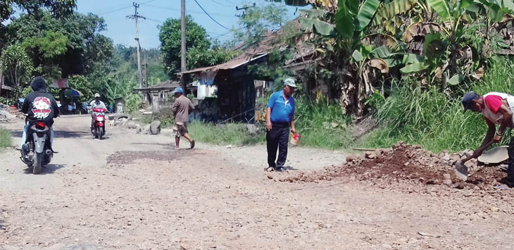GOTONG ROYONG: Warga Desa Padabeunghar, Kecamatan Jampangtengah, saat bergotong royong mengurug jalan berlubang dengan peralatan seadanya, Kamis (17/5).