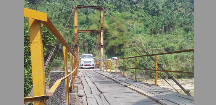 HATI-HATI: Sebuah kendaraan nampak berhati-hati saat melintasi jembatan Desa Bantarkalong, Kecamatan Warungkiara yang mulai rusak dan membahayakan.